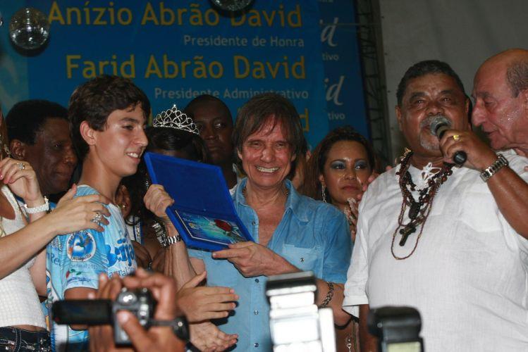 O cantor Roberto Carlos, homenageado da escola de samba Beija-Flor de Nilópolis no Carnaval 2011, visita pela primeira vez a quadra da escola, no Rio de Janeiro (4/2/2011). Na foto, Roberto segura placa da homenagem que recebe com o enredo