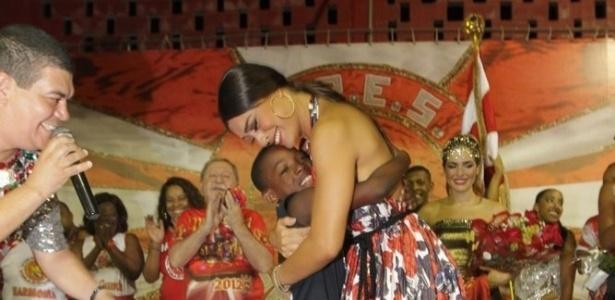 Juliana Paes abraça menino da comunidade ao receber o título de rainha da Viradouro na quadra da escola, em Niterói (24/1/12)