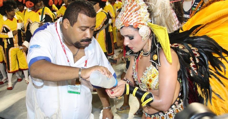A rainha de bateria da Viradouro, Monique Alfradique, se refresca em desfile na Sapucaí, no Rio de Janeiro (18/2/12)