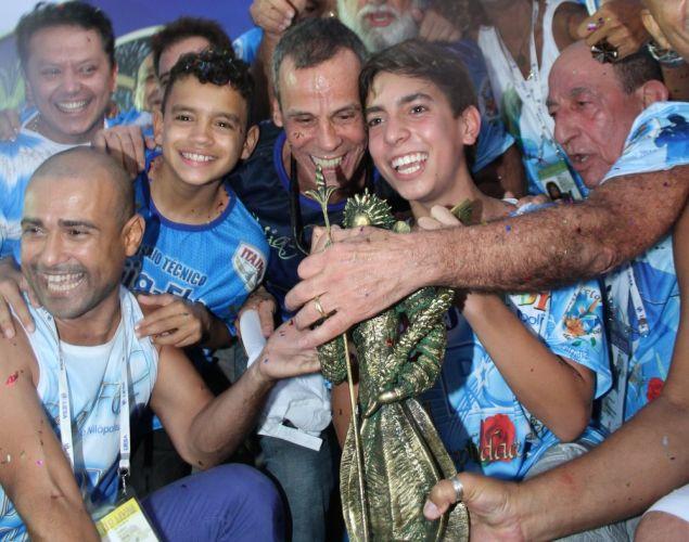 O coreógrafo Carlinhos de Jesus comemora junto a membros da escola de samba de Nilópolis o título da Beija-Flor (9/3/2011)