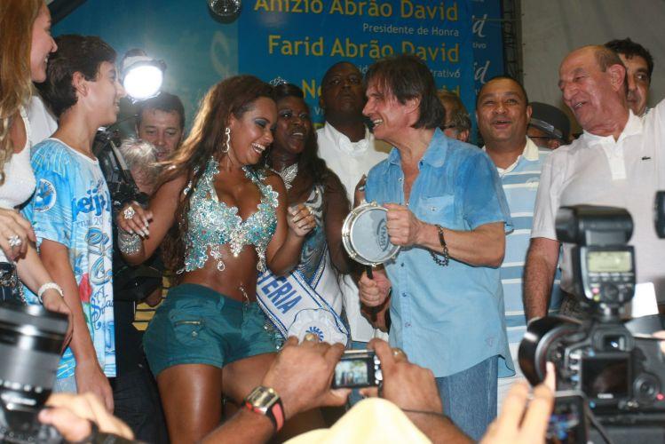 O cantor Roberto Carlos, homenageado da escola de samba Beija-Flor de Nilópolis no Carnaval 2011, visita pela primeira vez a quadra da escola, no Rio de Janeiro (4/2/2011). Na foto, Roberto toca tamborim para a rainha de bateria Raíssa Oliveira