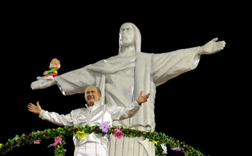O humorista Renato Aragão desfila em carro alegórico da X-9, escola que o homenageia neste Carnaval com o samba