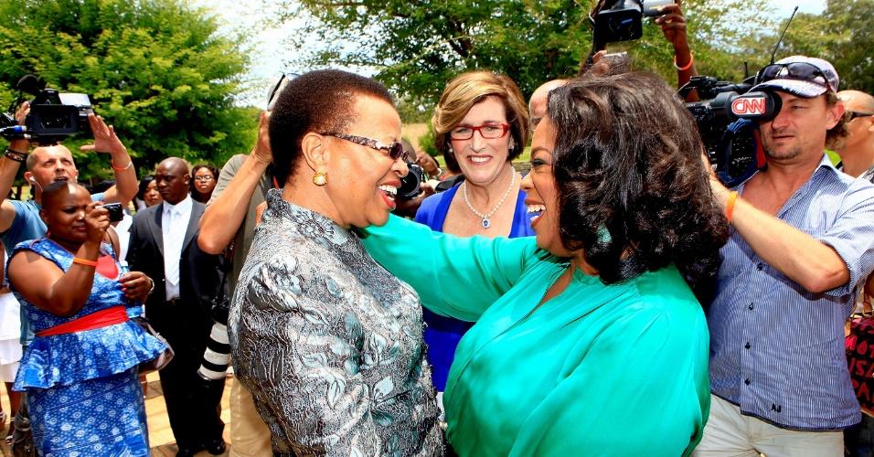 Oprah Winfrey cumprimenta Graça Machel, esposa do ex-presidente Nelson Mandela em Henley on Klip, África do Sul (14/1/12)