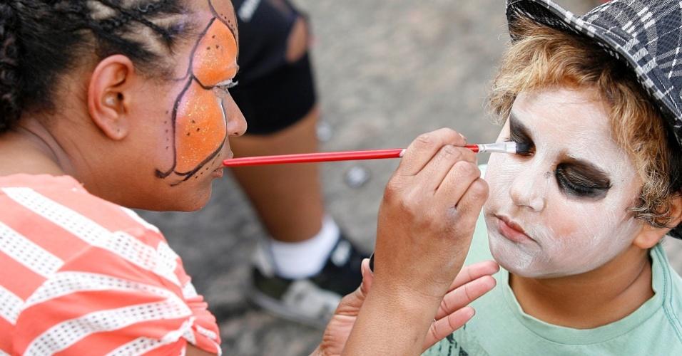 Mulher faz pintura no rosto de criança durante passagem do bloco Liga Pra Rádio em Ouro Preto (18/2/12)