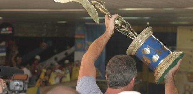 O carnavalesco Paulo Barros ergue troféu e comemora a vitória da escola carioca (22/2/12)